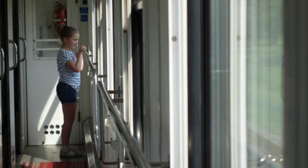 Un enfant  de l'exode, les mains contre la vitre où défile en accéléré le paysage ukrainien d'Est en Ouest.